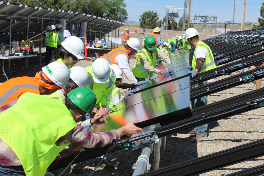 A group of people working on a community solar array.
