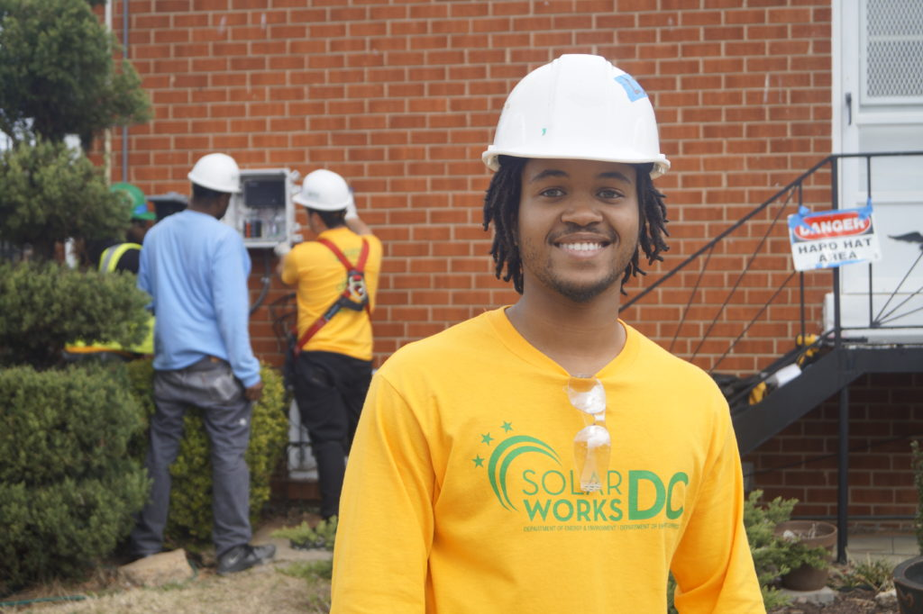 SolarWorks DC job trainee smiles as other participants work onsite.
