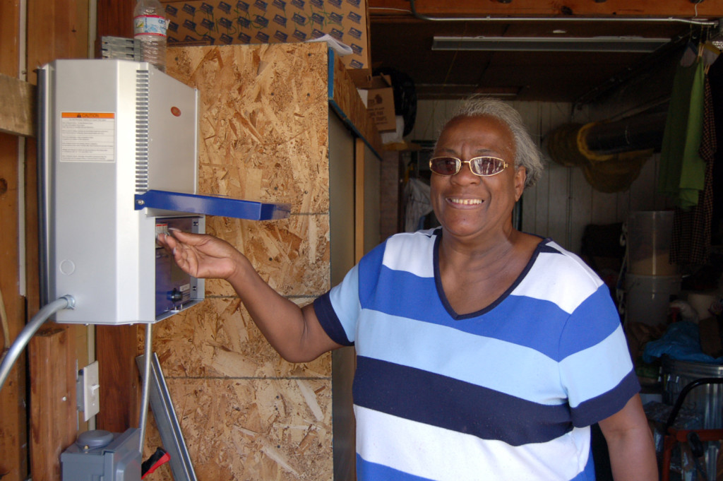 A smiling homeowner turns on the switch to her solar.