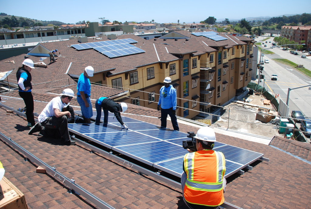 A group of workers installs solar on a multifamily affordable housing unit.