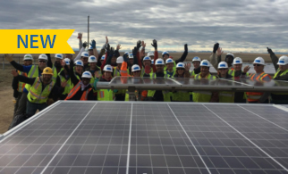 Volunteers celebrating in front of solar for Denver Housing Authority.