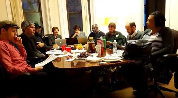 The 51st State Co-op participants meet around a table.