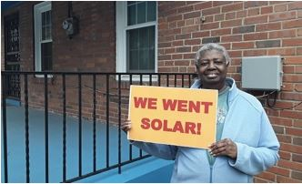 "Anna Butler smiles with a sign that reads ""We went solar!"""