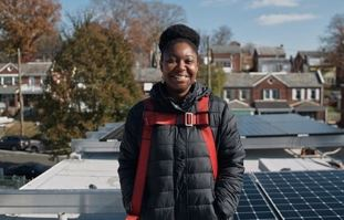 LaToya Smith stands in front of her newly installed solar system.